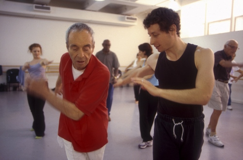 Martin Thall, a member of the Brooklyn Parkinson, dances with David Leventhal of the Mark Morris Dance Group. Photo by Katsuyoshi Tanaka.