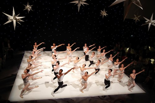 The performance, showing the entire company and stage. The luminescent dance floor looks like it is an excerpt of another dimension floating in space.