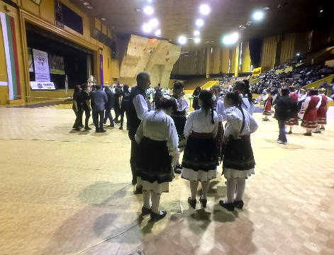 amateur, enthusiastic folk dancers preparing, waiting or performing for a panel of judges and the audience.