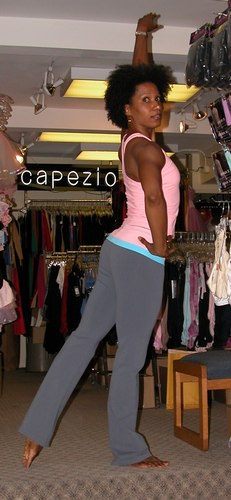 Pink petal top. Grey pants with pink and blue waistband. Clothing by AMMA. Modeled by Kendra Jackson. Available at <a href='http://www.onstagedancewear.com'>OnStageDancewear.com</a>.