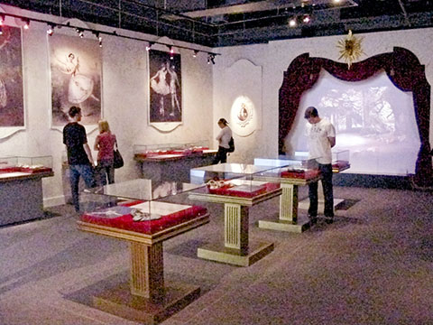 The exhibit space is dressed to create the feeling of classical ballet. Posters of famous dancers adorn the walls. A screen on a simulated stage projects video clips and display cases exhibit the history and craft of the ballet shoe.