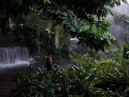 People sitting in a waterfall at the Arenal Resort