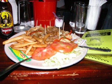 Still life with fajitas and fries, beer and menu