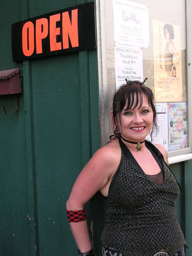 Employee Tammy Rose, on the Players Pub wait staff, beside the OPEN sign